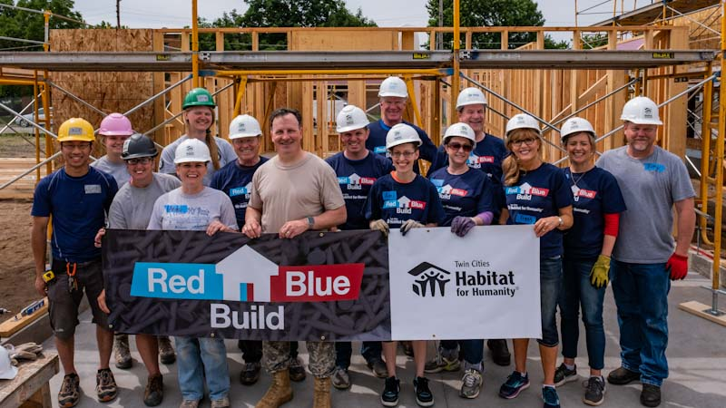"""Members from both parties of the Minnesota Legislature, wearing hard hats and gloves, standing in front of the frame of a house in the sunlight and holding a sign that says """"Red Blue Build, Twin Cities Habitat for Humanity."""""""