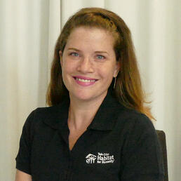 Robyn Bipes-Timm in front of a white background, smiling, wearing a black Habitat polo shirt.