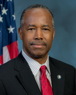 Ben Carson in front of a blue background and an American flag. He's wearing a black jacket over a gray and white striped dress shirt, with a red tied and a blue button on his left lapel.