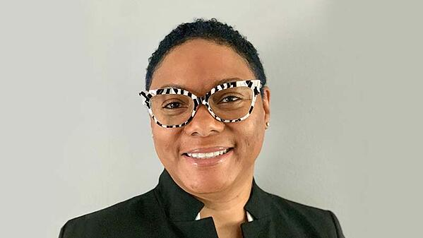 Shereese Turner smiling in front of a gray background, wearing a white shirt, black formal jacket, and black and white striped glasses.