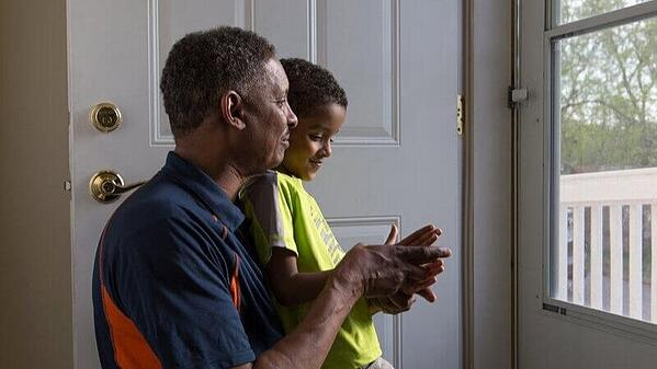 A Habitat homeowner sitting with his son, looking out their front door.