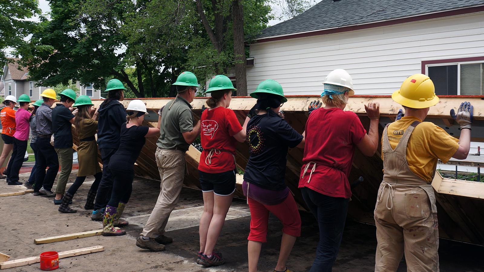 Sunrise Banks volunteers raising a wall in 2016