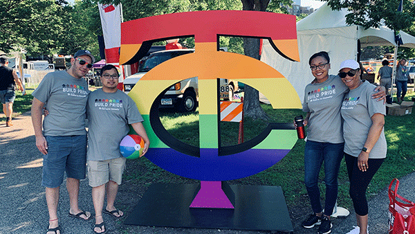 "A rainbow sign saying ""TC"" with the T intersecting the C. Four Habitat employees in gray t-shirts that say ""Build Pride"" with a rainbow on them stand flanking the sign. They are outside at TC Pride festival."
