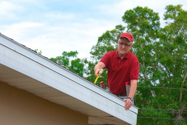 Man with a hammer fixing a roof