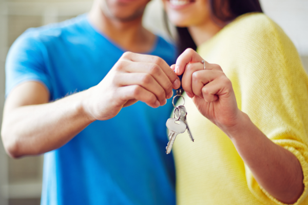 a couple holding a set of keys, zoomed in on their hands