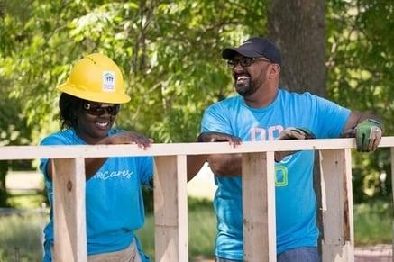 Two volunteers laughing.