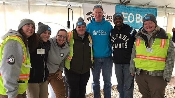 AmeriCorps members wearing Winter Warriors hats and posing with Chris Coleman at the CEO Build.