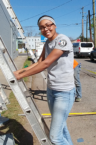 AmeriCorps volunteer steadying a ladder.