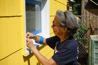 A U.S. Bank volunteer smiles while painting Cassandra's home.