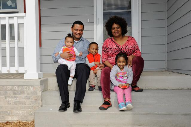 Melkamu and Fasika and family in front of their new home.