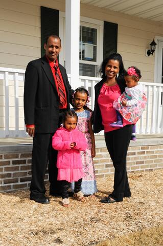 Samson and Margitu and family in front of their new home.