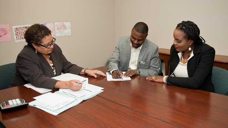 Fred and Brigitte signing papers with their financial coach, Linda White, at Model Cities.