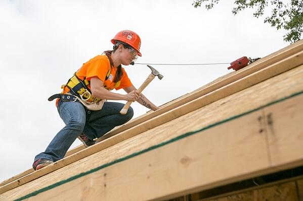 A woman from Andersen's Women Build team hammering on the roof