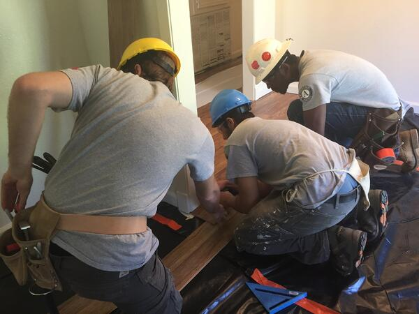 AmeriCorps members laying floors
