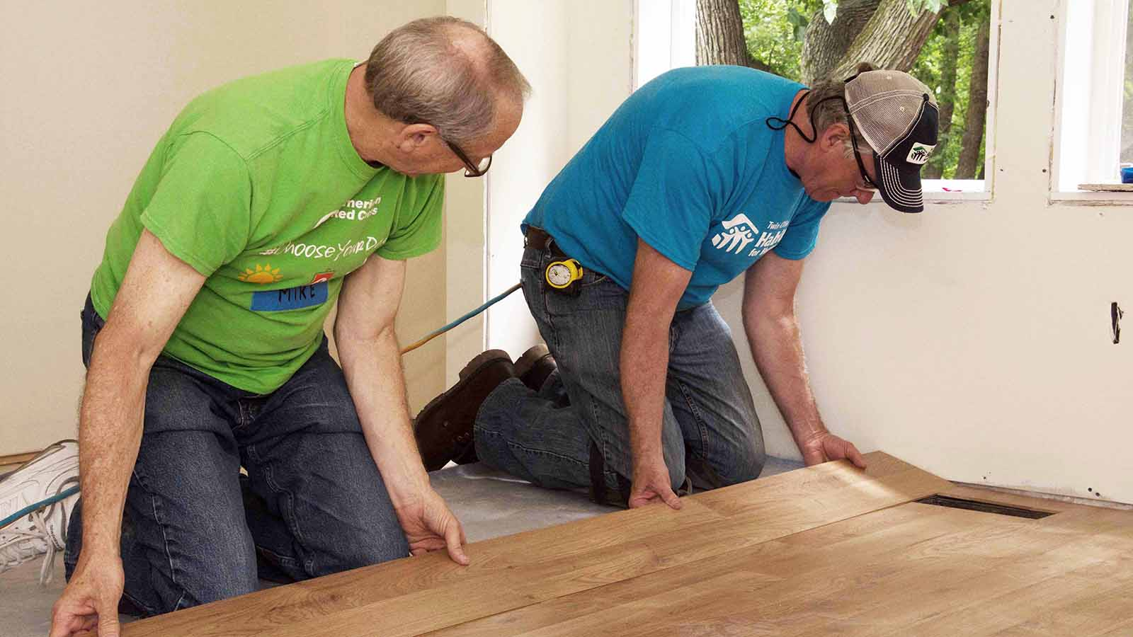 Chris learning to install flooring from a Holy Hammers volunteer