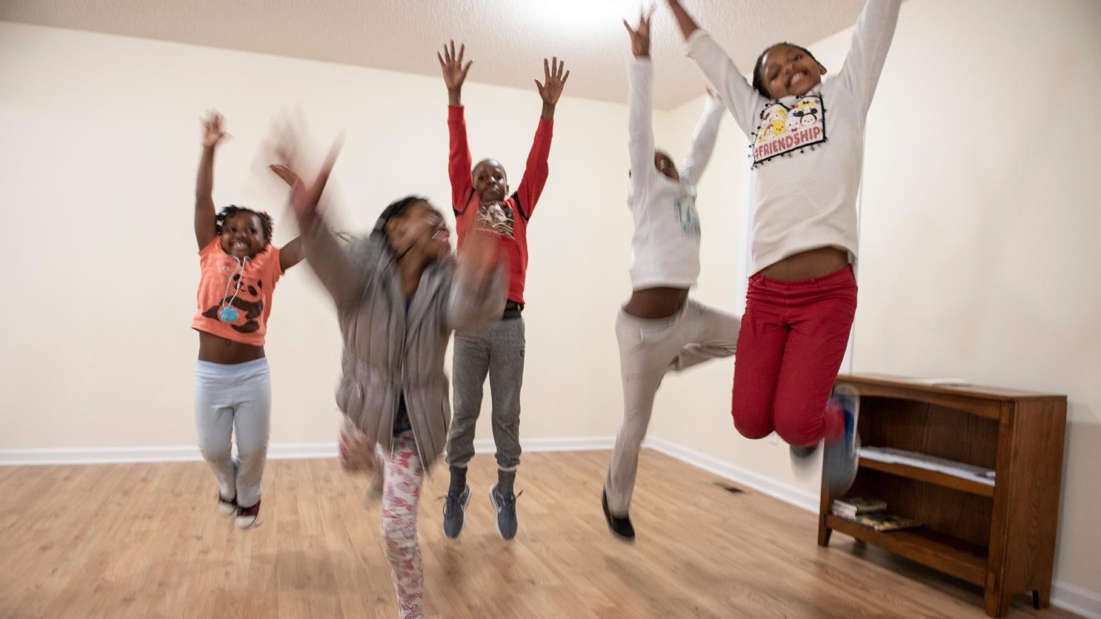 Kids jumping at a home dedication