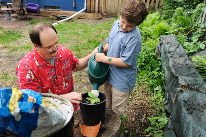Erik and his dad watering a plant