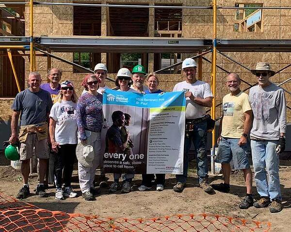 A group of volunteers holding the site sign for the home they're building.