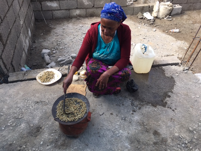 A woman roasting coffee beans.