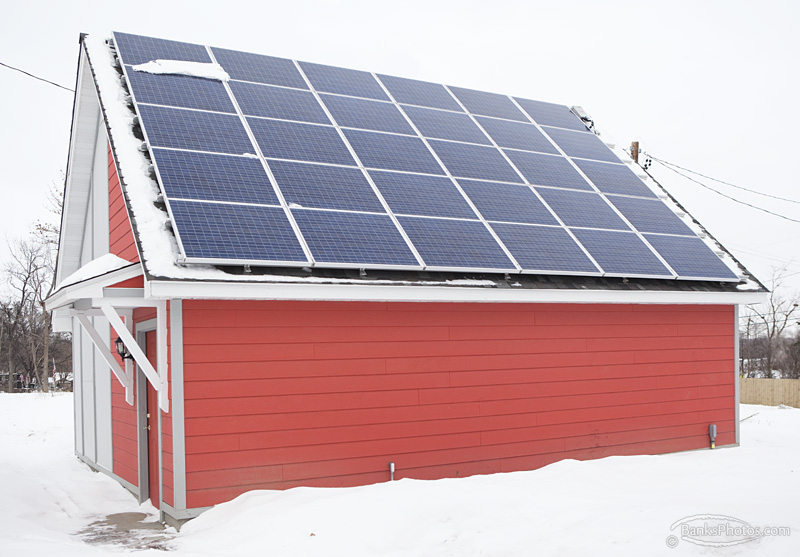 A bright red shed in the snow, with solar panels on the roof.