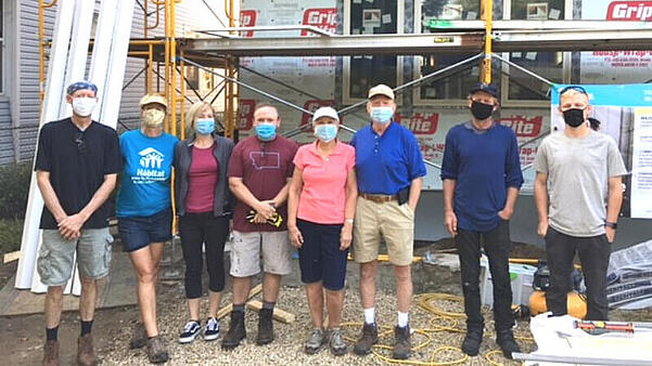 The Olson family and friends volunteering together on the home they sponsored. Karen is in the middle (pink shirt), with David next to her (blue shirt).