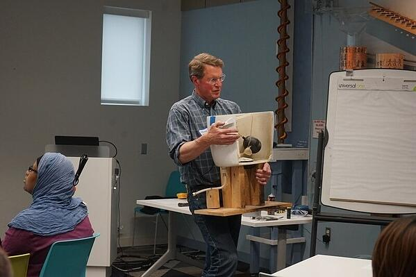 Steve showing the back of an exposed toilet tank to explain the parts.