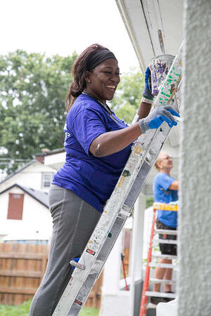 A volunteer painting a house.