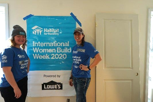 """Two women in blue Women Build Week t-shirts next to a blue sign that has the TC Habitat logo and the text """"International Women Build Week 2020"""". Below the text is a section that says """"Powered by Lowe's""""."""