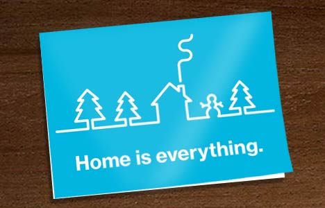"""card for tribute gifts in blue, with white text saying """"Home is everything."""" A white line drawing of a winter landscape with trees, a house, and a snowman is above the text."""