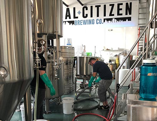 Two employees at Dual Citizen Brewing Company's brewery working.