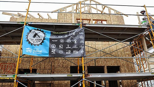 The House that Beer Built itself, with exposed walls and surrounded by construction platforms and the House that Beer Built promotional flag in light blue and black.