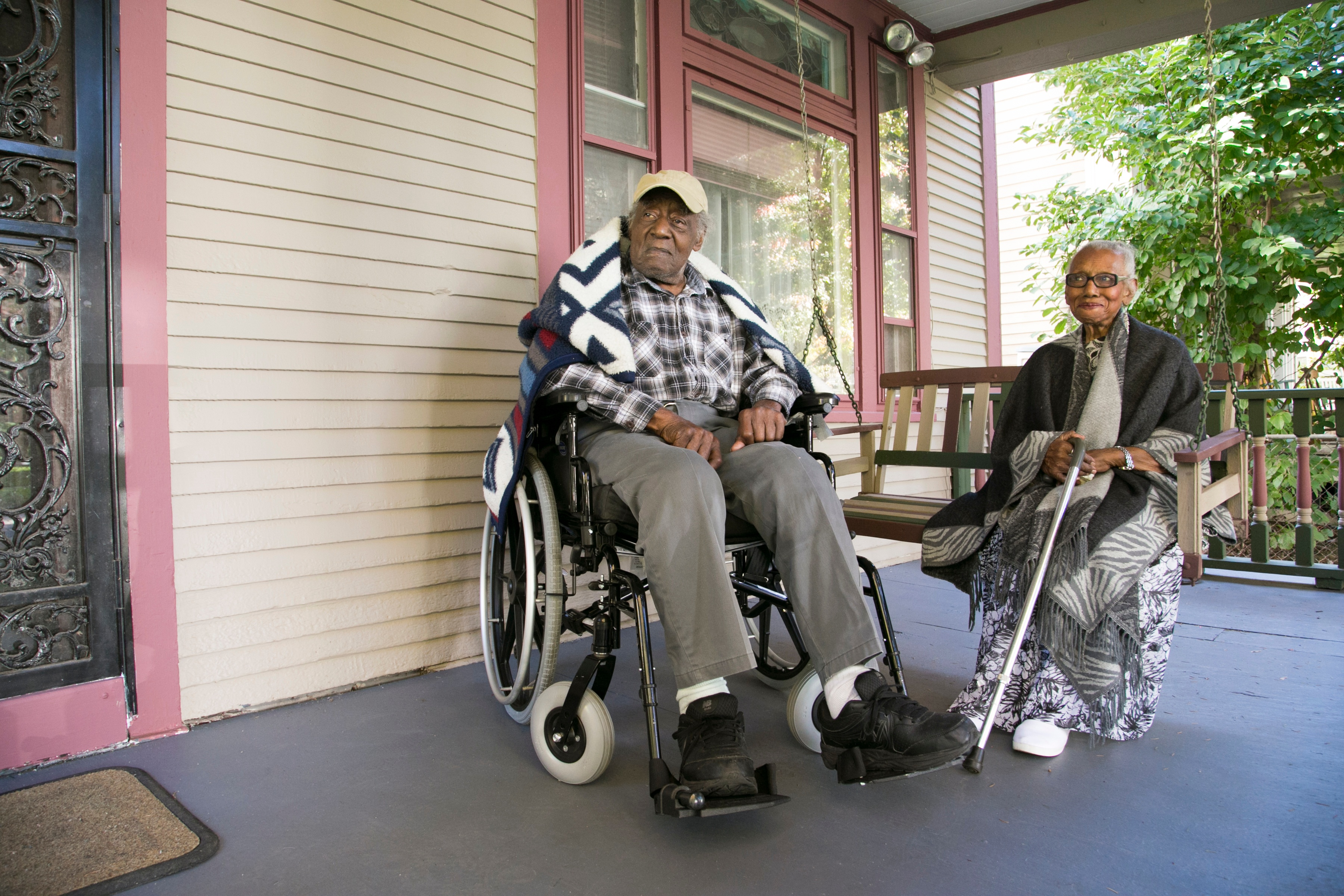Senior couple on porch swing and in wheel chair