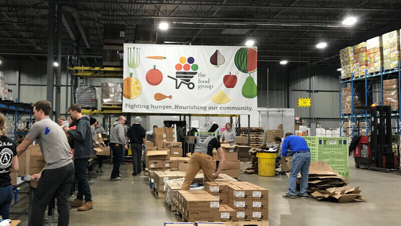 Volunteers moving boxes of food under the Food Group's banner in their warehouse.