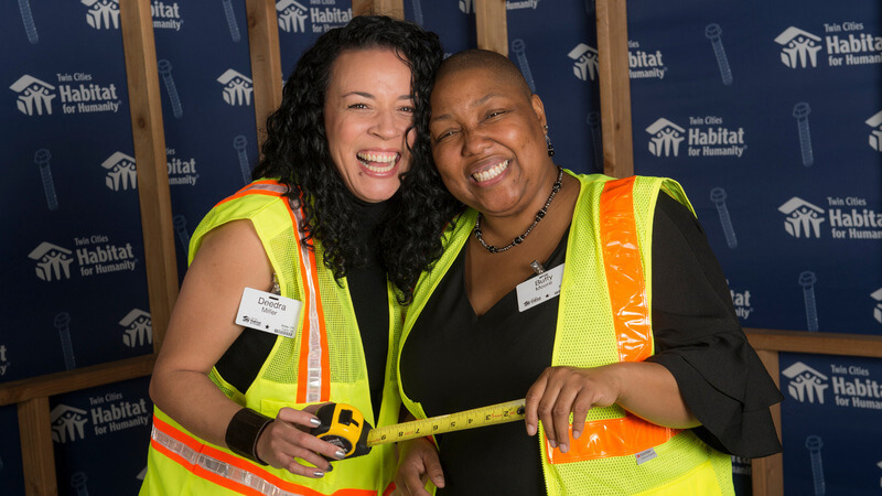 Two HHBT attendees in safety vests, holding an extended tape measure.