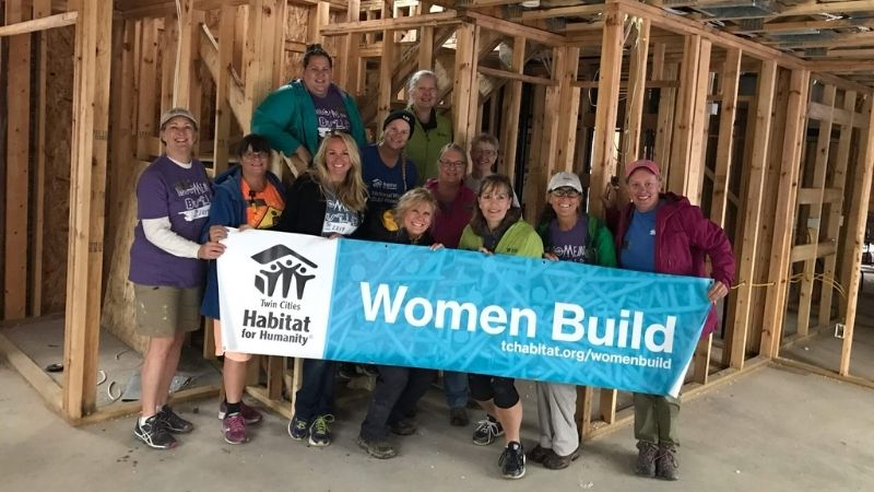 The Women Build Committee holding a Women Build banner in front of a the framing for a house.