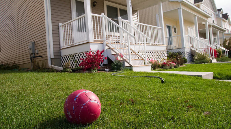 A beige house with a front yard. A red soccer ball sits on the front yard.