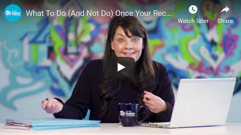 "A YouTube preview image, with Jen LaCroix sitting at a desk speaking in front of a colorful background. The white text at the top reads ""What To Do (And Not Do) Once Your Rec..."" There is a laptop, a blue Habitat coffee mug, and a pile of documents on the desk."