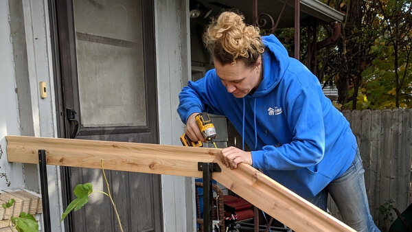 Age Well at Home project supervisor Ashley Realbanas installing a railing at a home