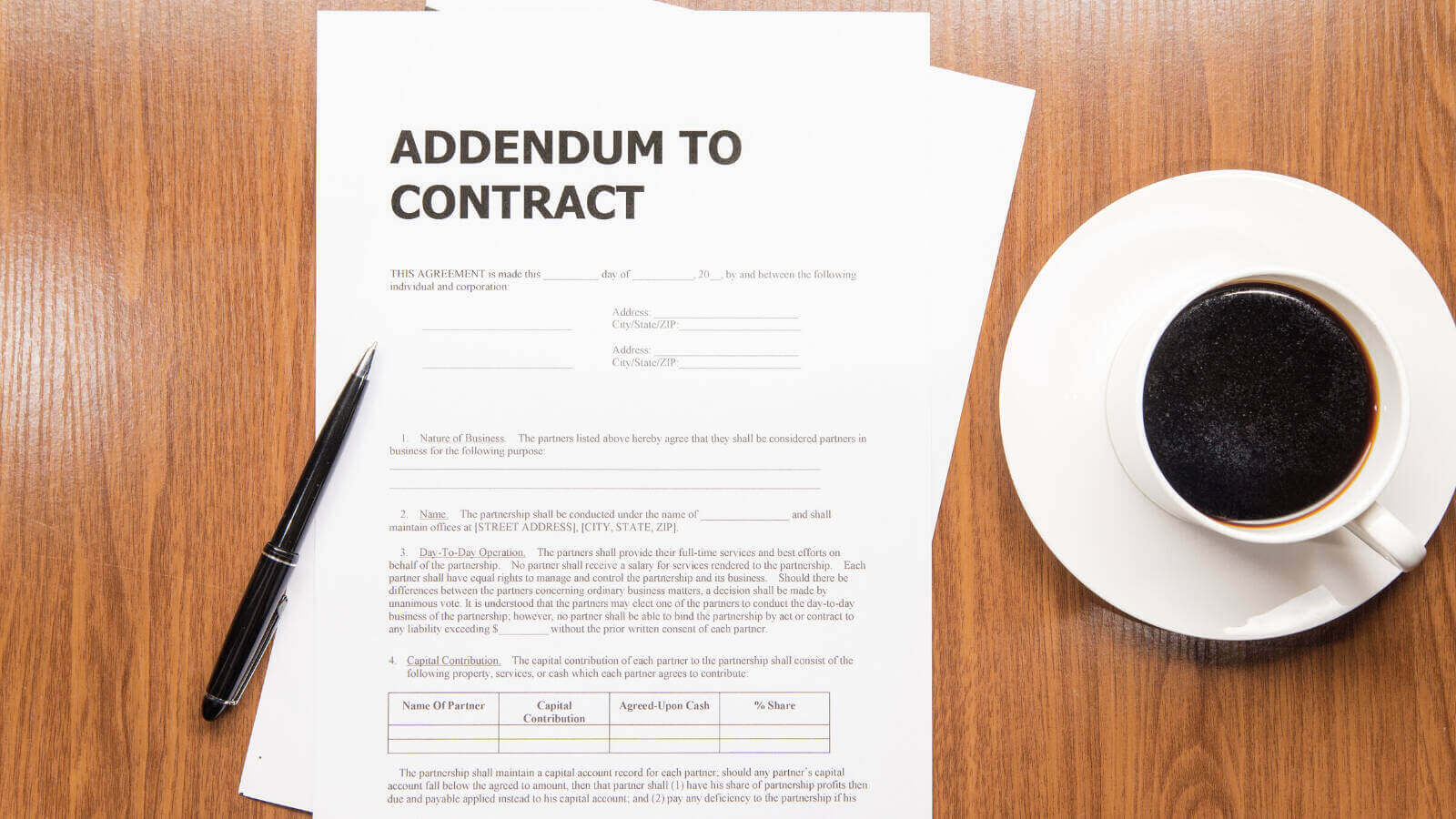 """On a wooden background, a couple sheets of white paper with the words """"ADDENDUM TO CONTRACT"""" at the top and an unreadable form below. A black pen sits atop the paper. A cup of black coffee on a saucer sits to the right."""