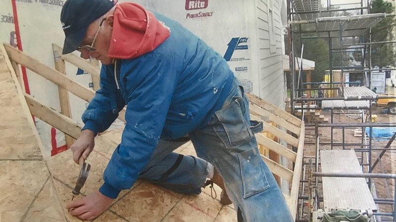 Ken hammering nails on a roof, in blue jeans, a blue jacket, red hoodie, and a black baseball cap.