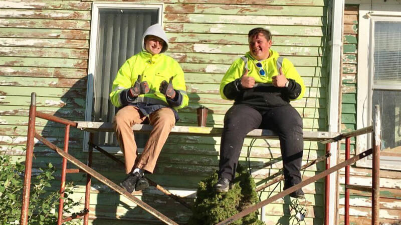 Two Summer AmeriCorps members sitting on a construction platform, giving the thumbs-up sign and wearing yellow safety jackets.
