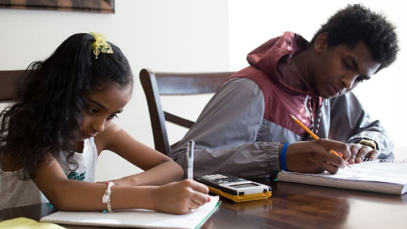 Two siblings sitting at a kitchen table doing homework with a calculator.