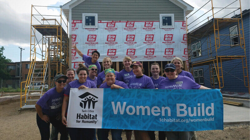 A group of volunteers holding the Women Build banner in front of an in-progress house.