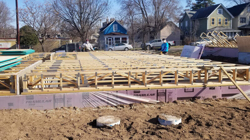 A Habitat employee and AmeriCorps member working on framing a house.