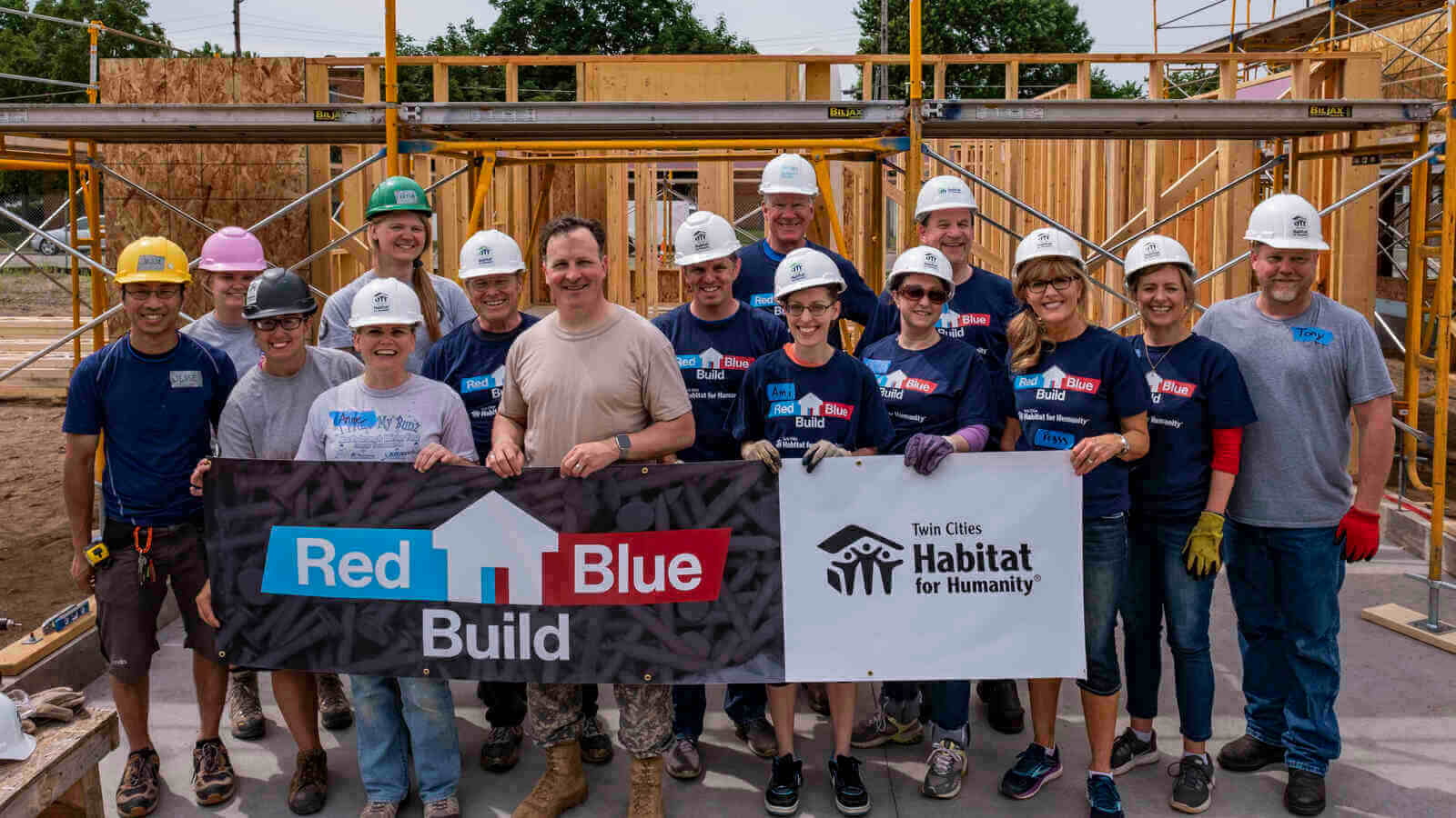 "Members from both parties of the Minnesota Legislature, wearing hard hats and gloves, standing in front of the frame of a house in the sunlight and holding a sign that says ""Red Blue Build, Twin Cities Habitat for Humanity."""