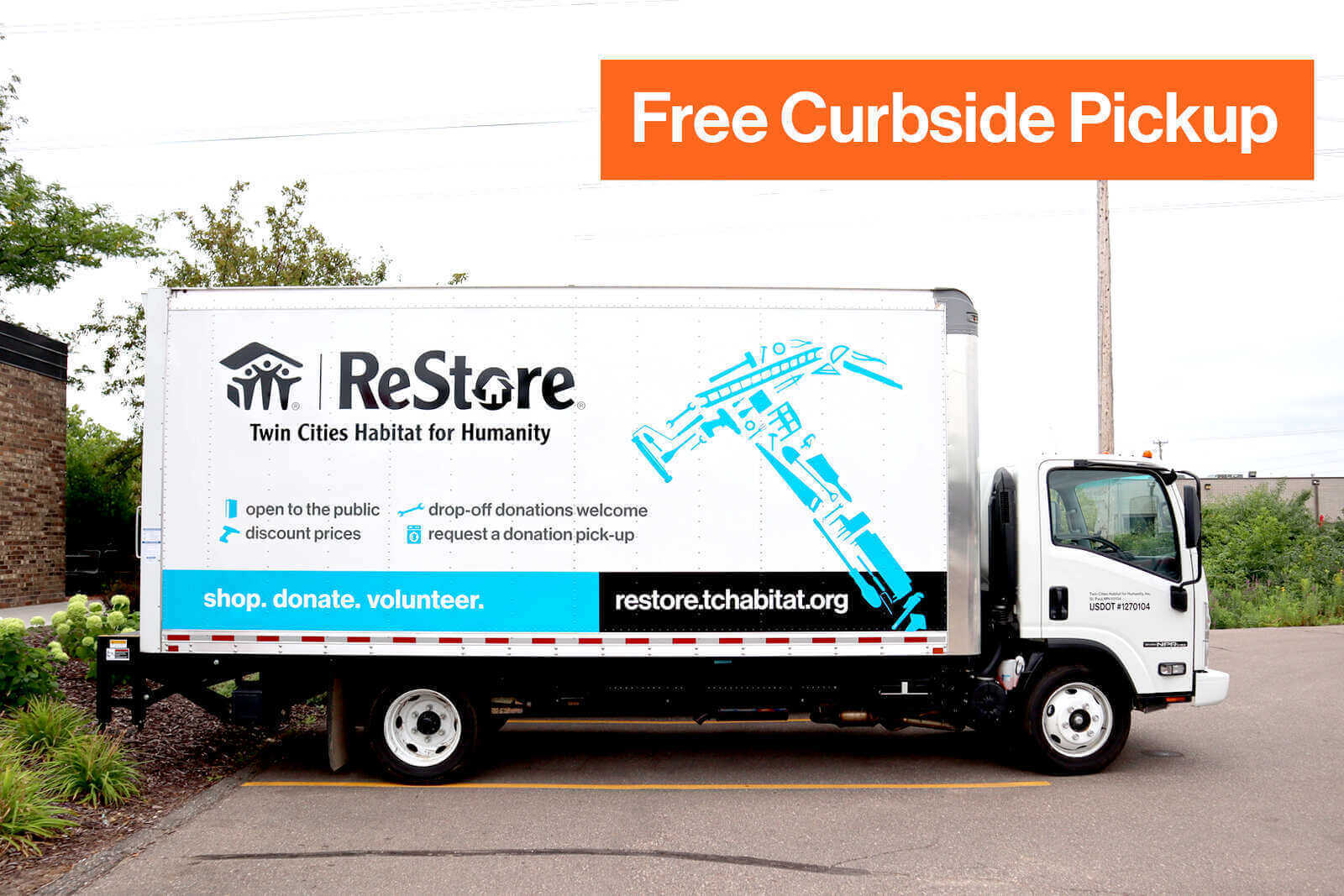 "Outside on a parking lot sits a white truck that has the ReStore logo, a large light blue hammer made up of many tools, a blue bar at the bottom that says ""shop. donate. volunteer."", a black bar to the right of it that says ""restore.tchabitat.org"". Above the bar on the truck is a series of short phrases next to light blue icons, saying ""open to the public"", ""discount prices"", ""drop-off donations welcome"", and ""request a donation pick-up"". Overlaying the image is an orange box saying ""Free Curbside Pickup"""
