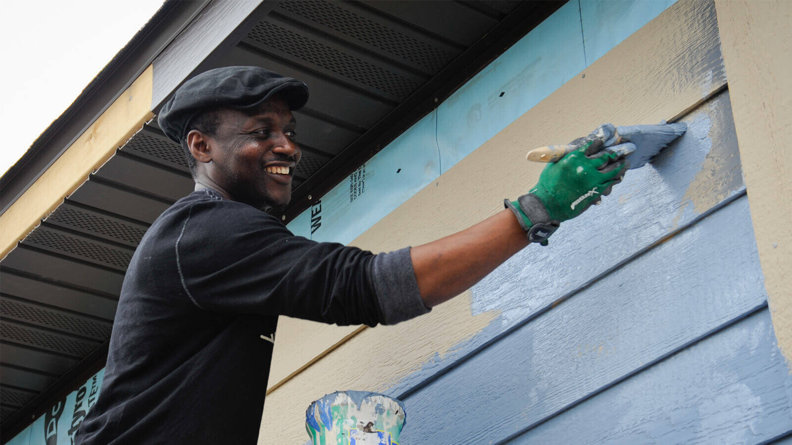 A man smiling as he brushes light blue paint on a tan house, just below the roof. He wears a black long-sleeved shirt, a black hat, and green work gloves. There is a can of paint below his raised arm.