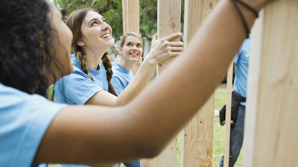 Group of teens volunteering on a home build with habitat.