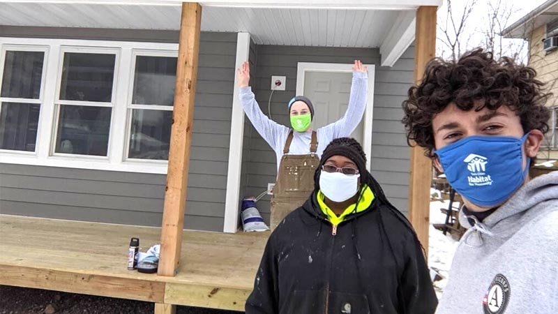 Image of a site supervisor and AmeriCorps service members on a front porch of a Habitat homebuilding site.