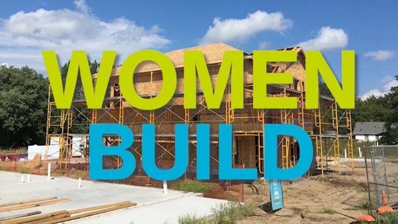 "The words ""Women Build"" in green and blue letters in front of in-progress house."